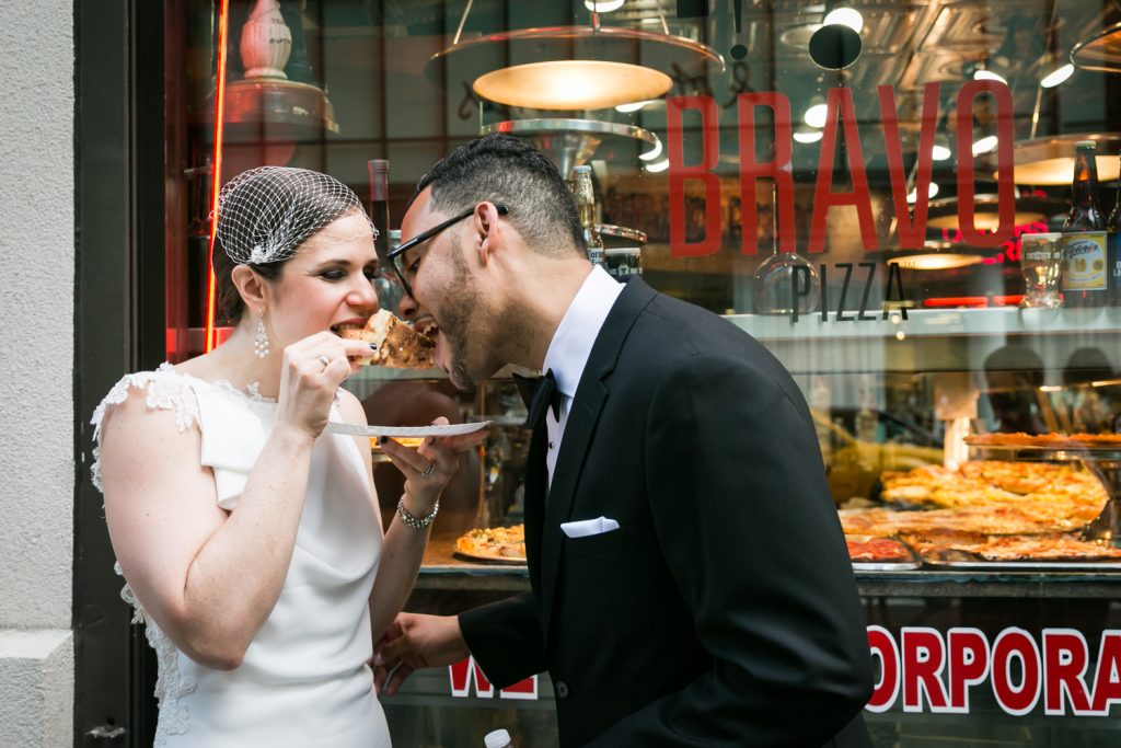 Bride and groom eating pizza on the street