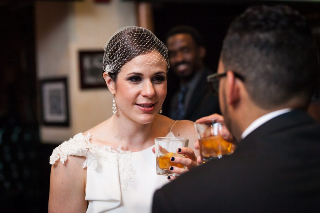 Bride looking at groom while drinking whiskey