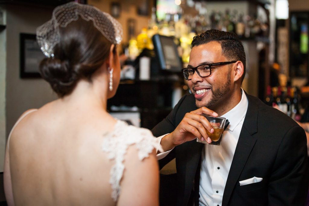 Groom laughing with drink in hand