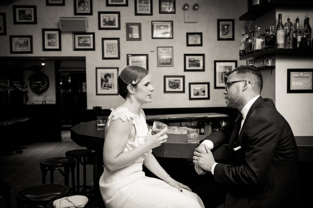 Black and white photo of bride and groom sitting at bar drinking