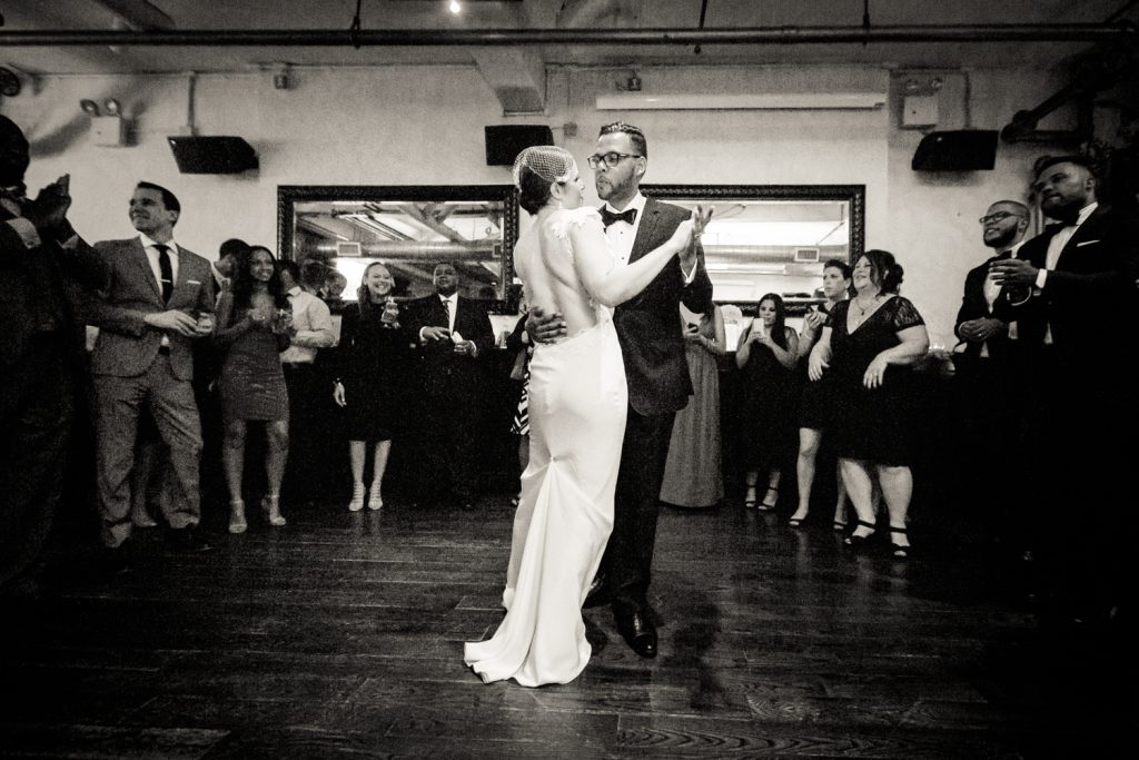 Black and white photo of bride and groom during first dance at wedding reception