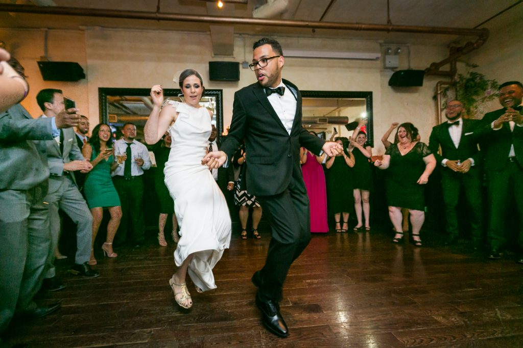 Bride and groom jumping in the air on the dance floor