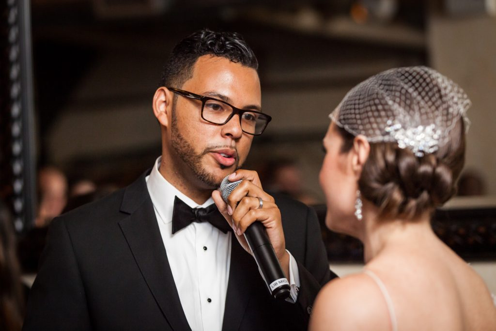 Groom using microphone to speak to bride