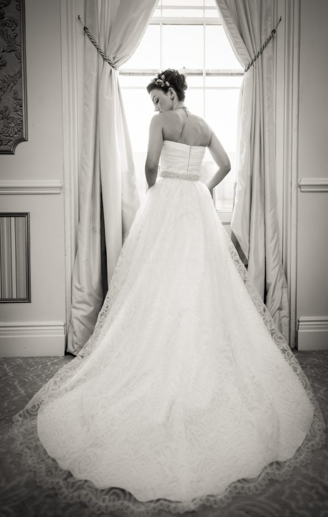Black and white photo of bride in wedding dress at window at a Snug Harbor wedding