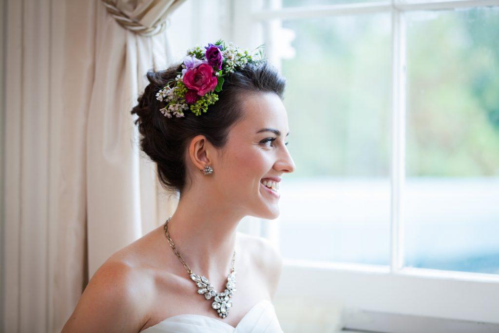 Bride wearing flower crown looking out window at a Snug Harbor wedding