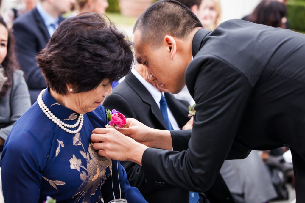 Groom pinning flower to his mother at a Snug Harbor wedding