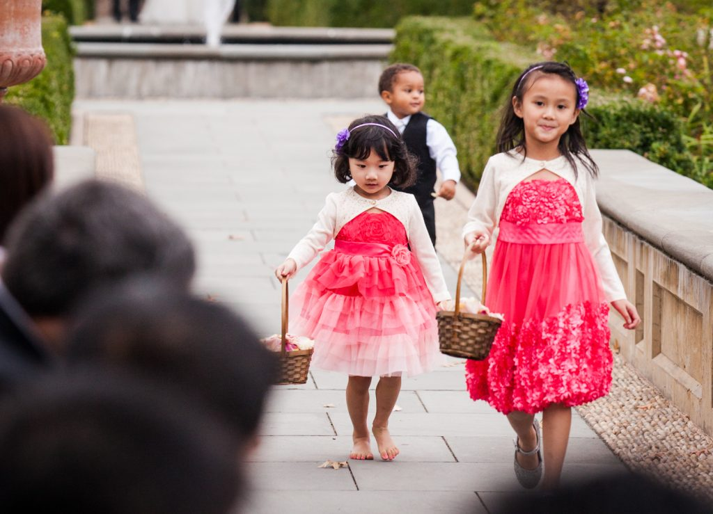Two little flower girls and ring bearer walking down aisle at a Snug Harbor wedding