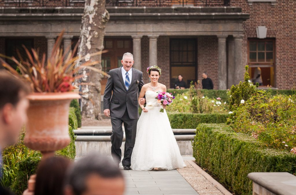 Bride and father walking down aisle in Tuscan Garden at a Snug Harbor wedding