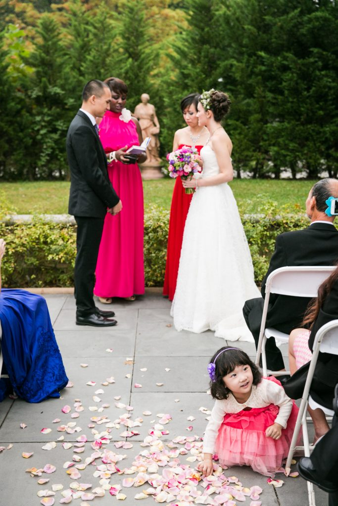 Bride and groom exchanging vows and little girl picking up flowers