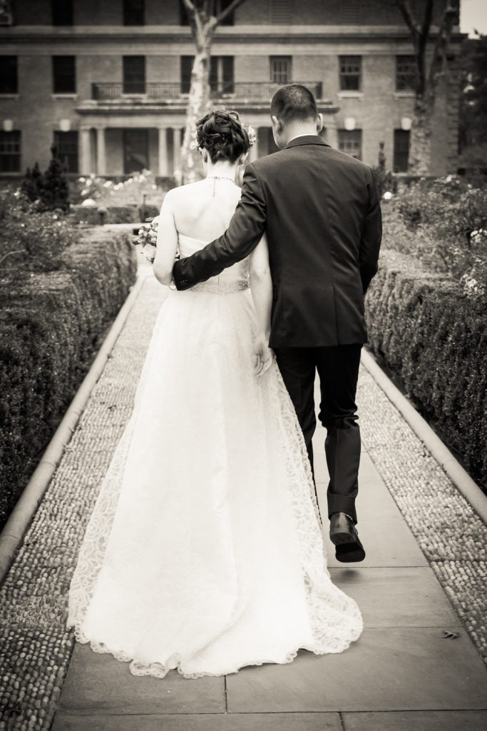 Black and white photo of bride and groom walking down aisle in Tuscan Garden