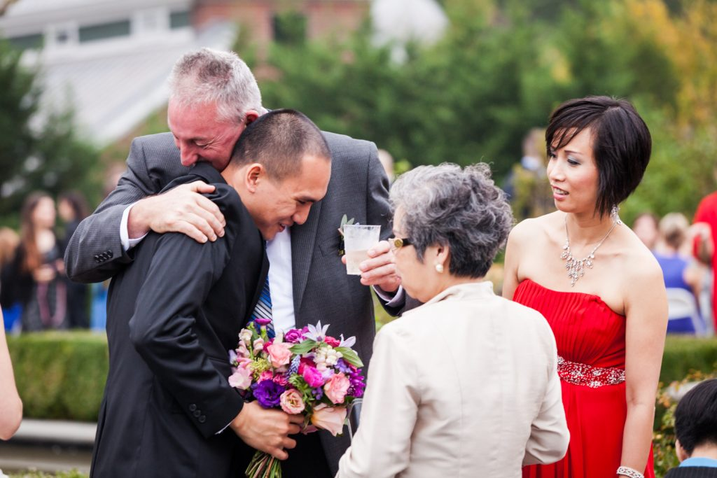 Groom hugging guest at cocktail hour
