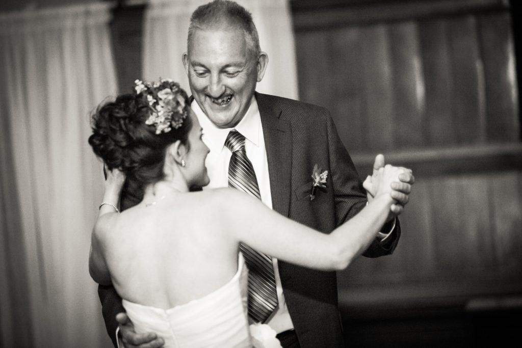 Black and white photo of bride dancing with her father