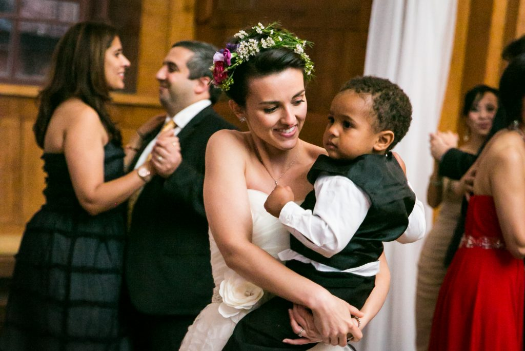 Bride dancing with little boy in her arms