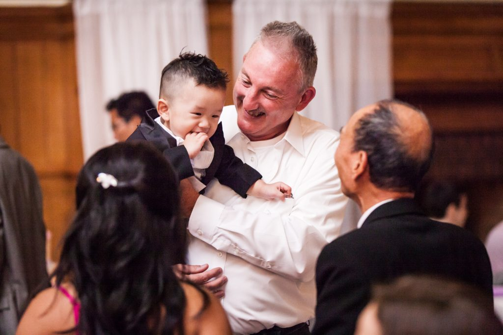 Father of bride dancing with little boy in his arms at a Snug Harbor wedding