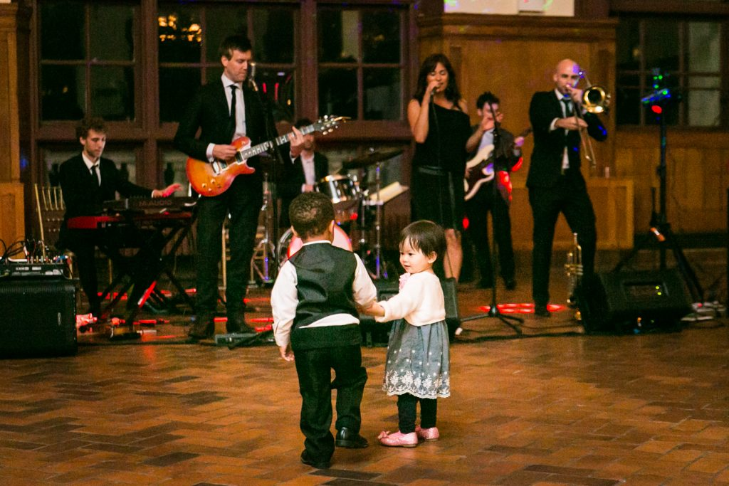 Two little kids holding hands in front of live band at a Snug Harbor wedding