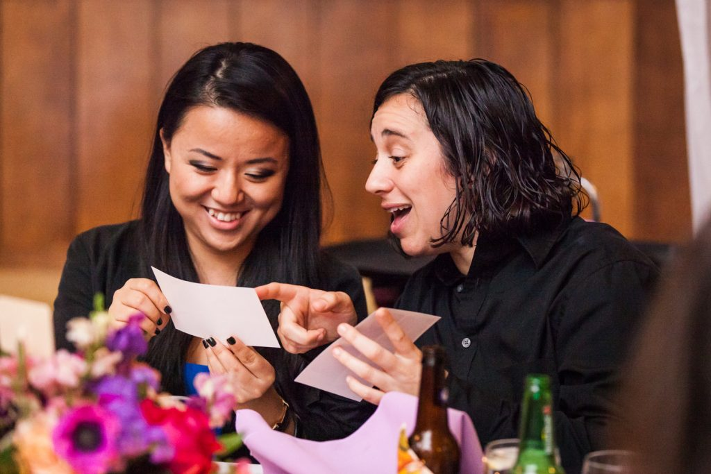 Two female guests laughing at a photo
