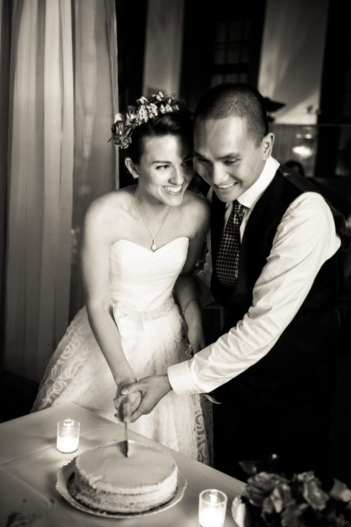 Black and white photo of bride and groom cutting cake at a Snug Harbor wedding