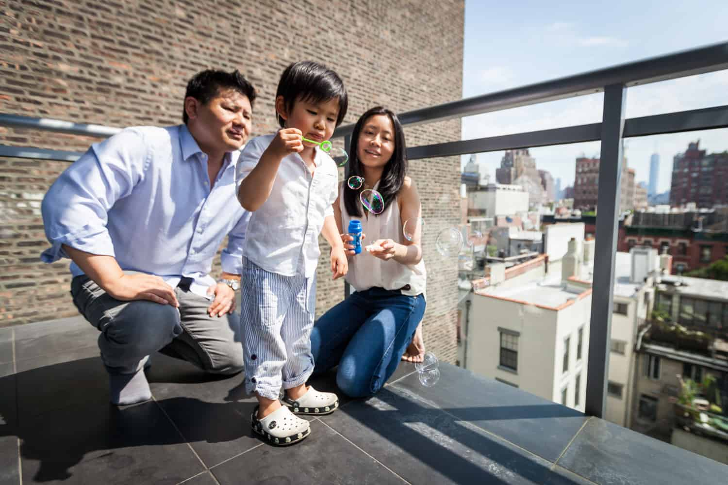 Chelsea family portrait of parents and little boy blowing bubbles on terrace
