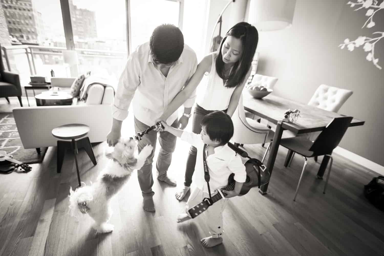 Black and white photo of parents and little boy playing with dog