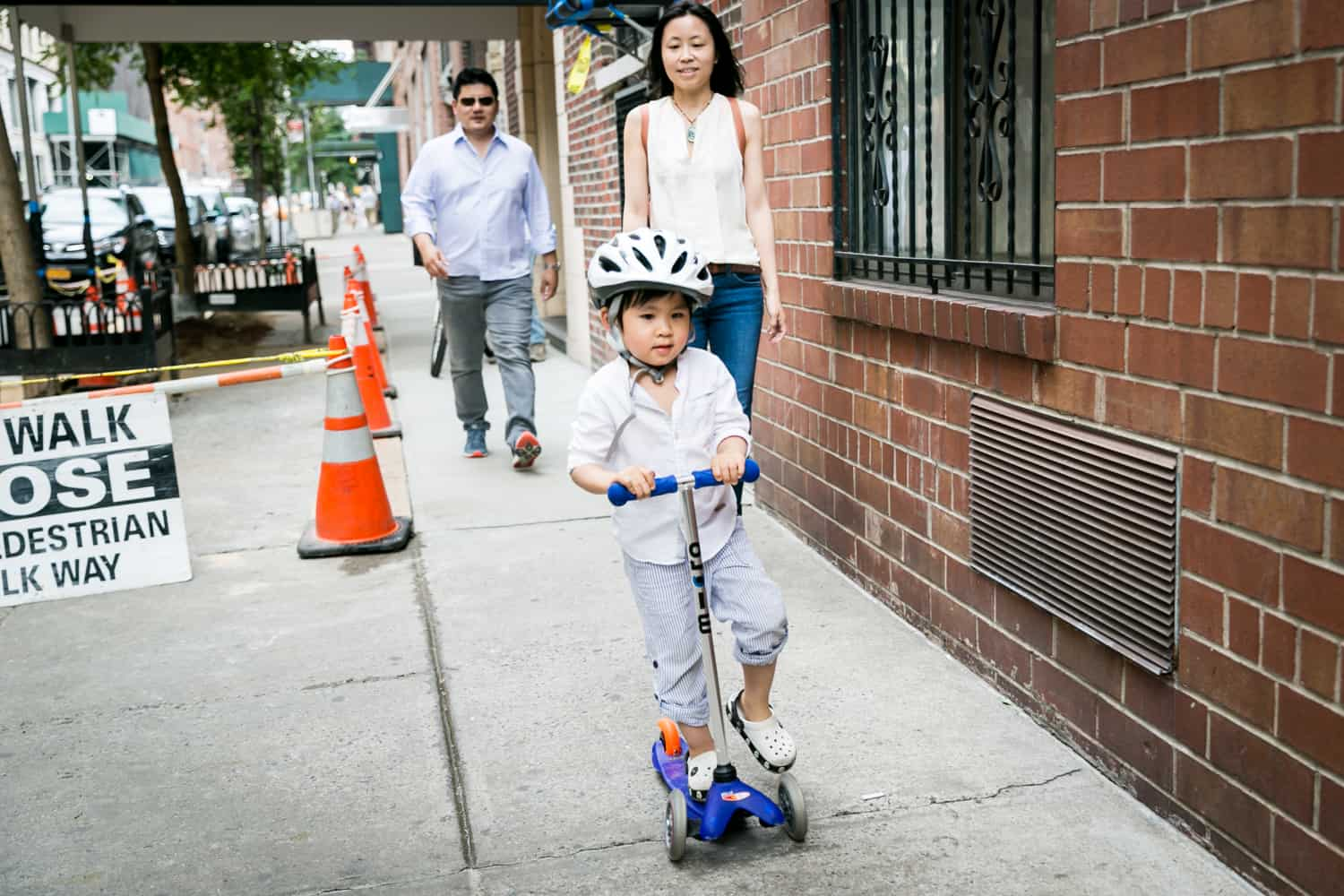 Parents and little boy on scooter on Manhattan sidewalk