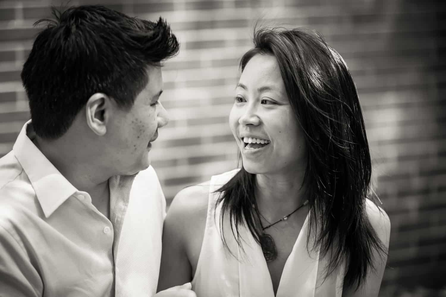 Black and white photo of parents talking in front of brick wall