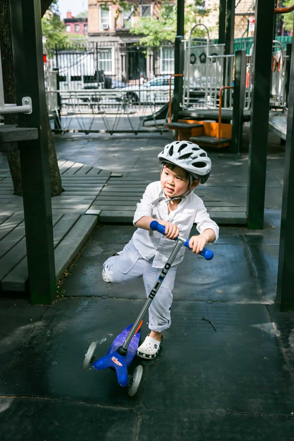 Little boy on scooter wearing bike helmet in playground