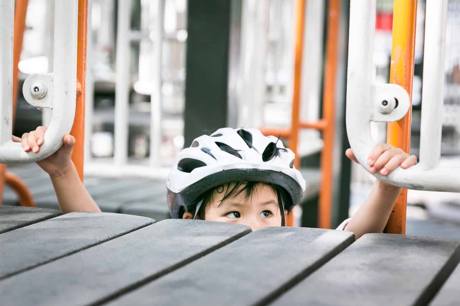 Little boy wearing bike helmet peeking over edge of playground
