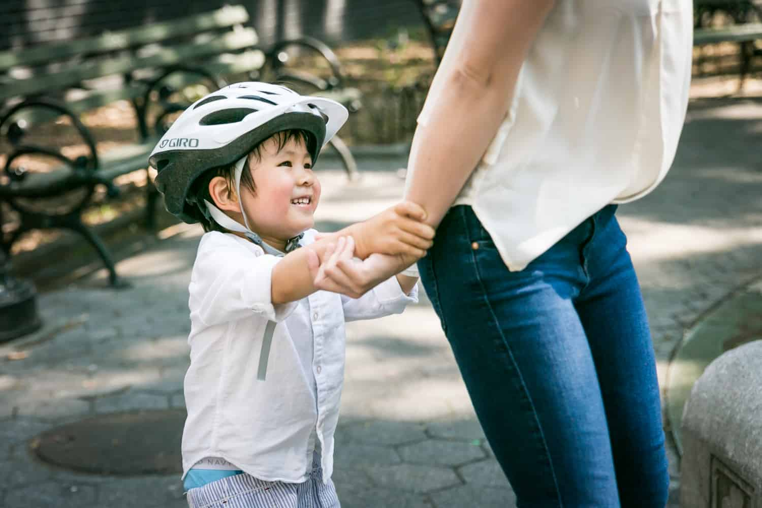 LIttle boy wearing bike helmet playing with mother