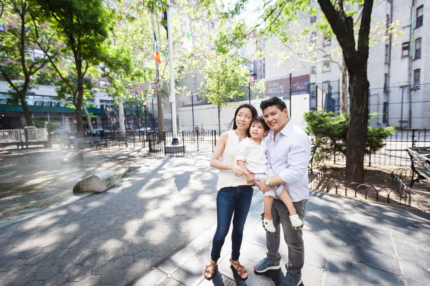 Chelsea family portrait of parents holding little boy in park