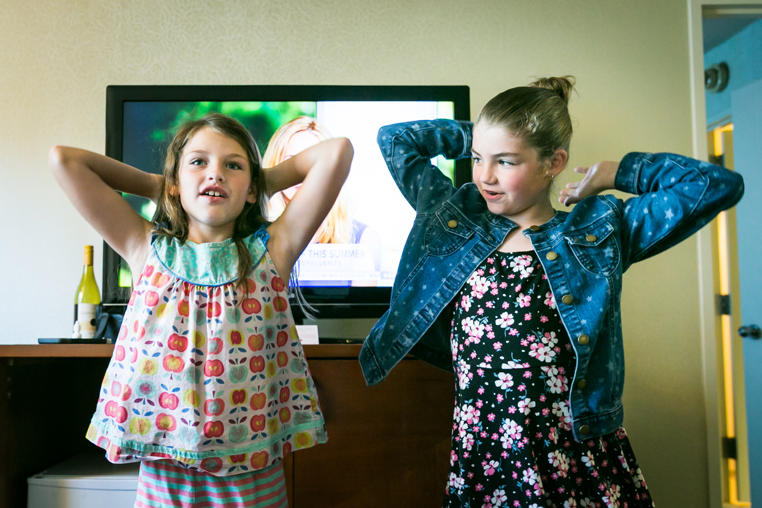 Two little girls dancing with arms up in a hotel room