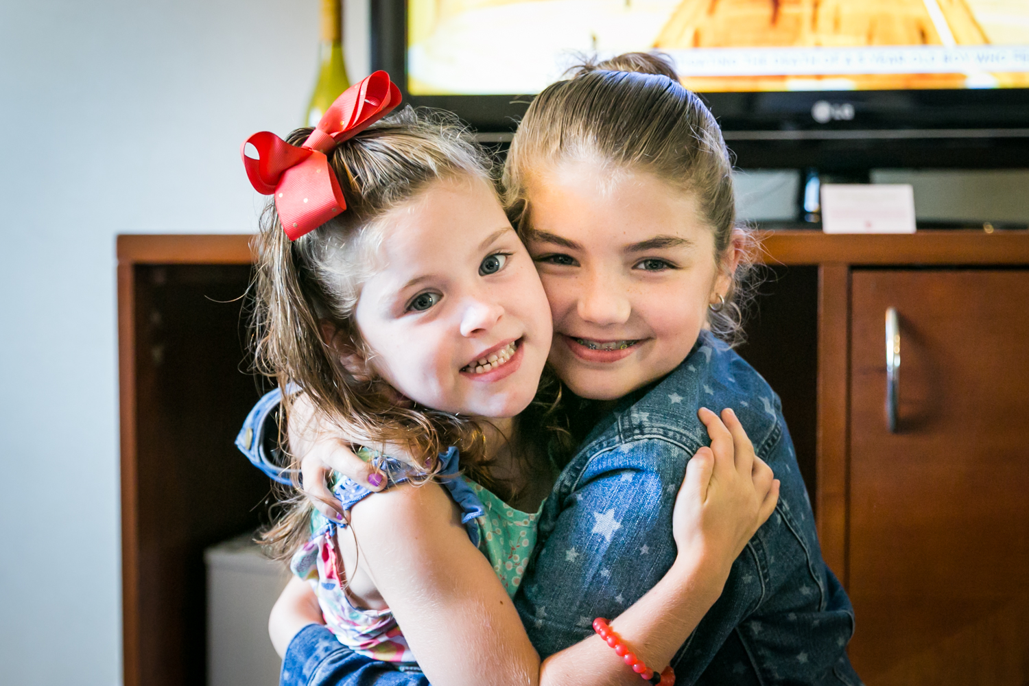 Two little girls hugging in a hotel room