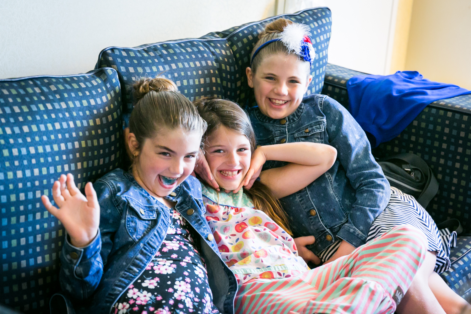 Three little girls playing around on a sofa