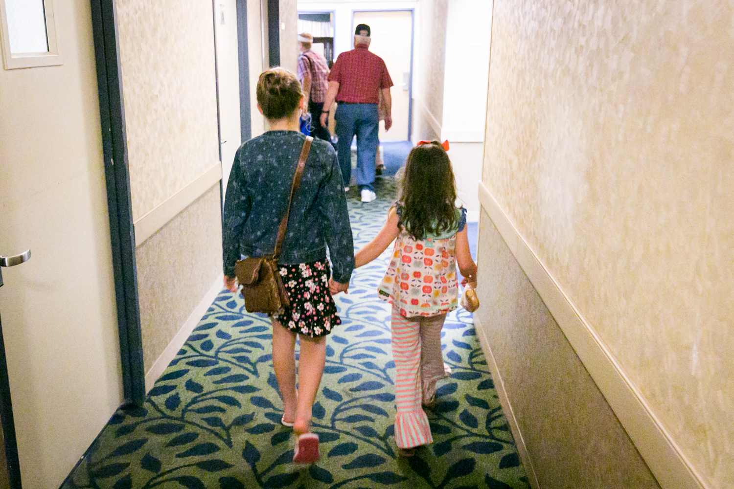 Two little girls holding hands walking down a hallway