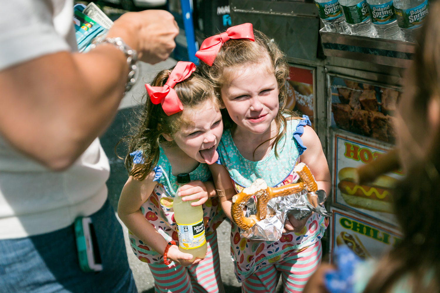 Two little girls making funny faces and holding a pretzel