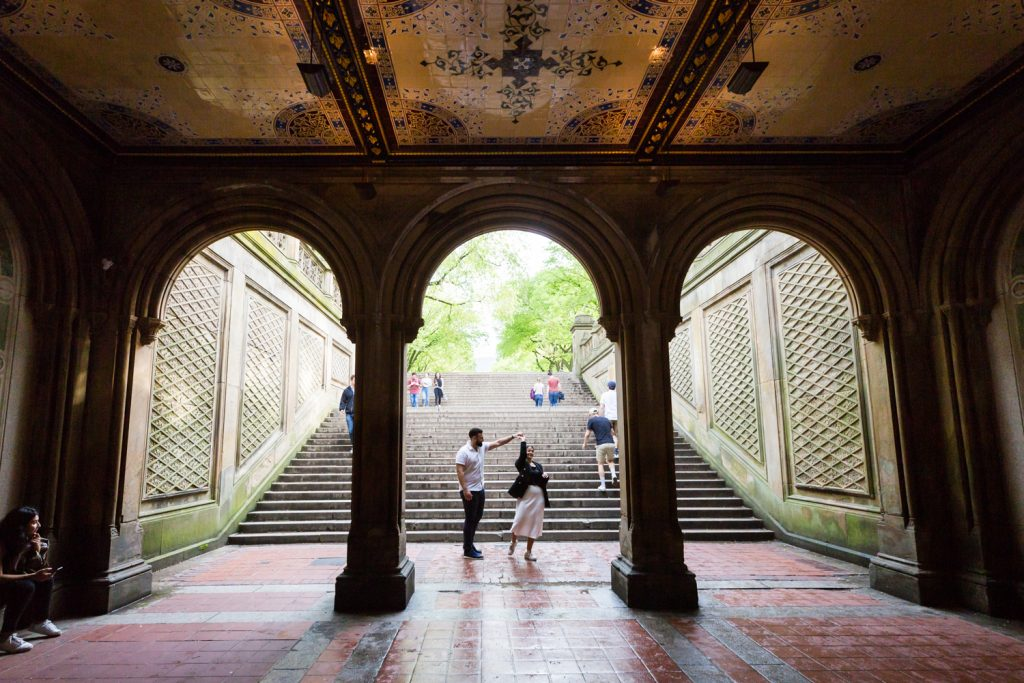 Couple dancing under mosaic arch in Central Park for an article on NYC rainy day photo tips
