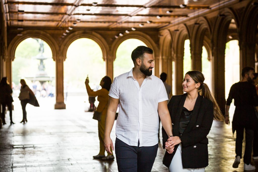 Couple walking hand in hand under mosaic arch in Central Park