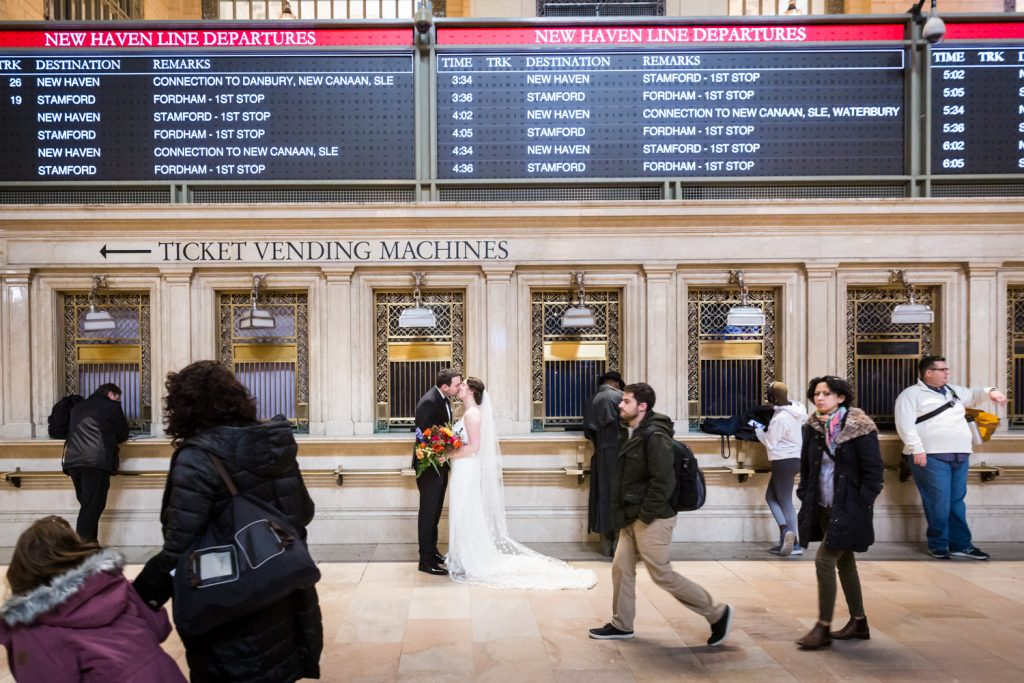 Bride and groom kissing in front of train timetables in Grand Central Terminal