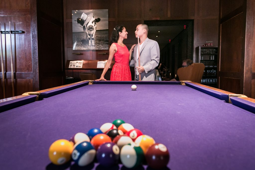 Couple looking at each other behind pool table