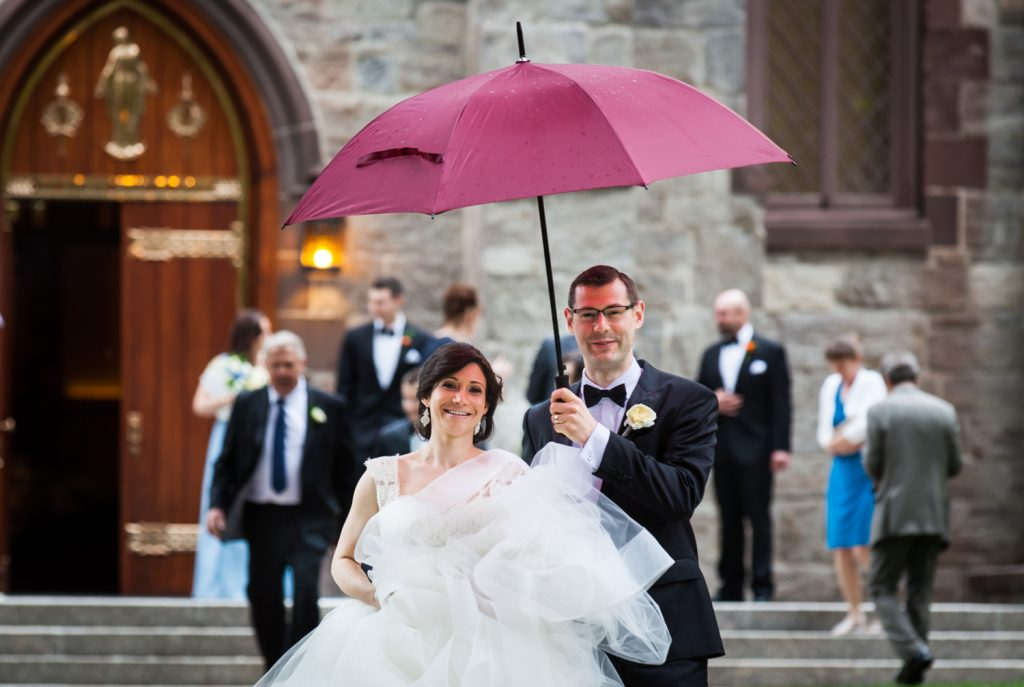 Bride and groom walking in rain under red umbrella for an article on NYC rainy day photo tips
