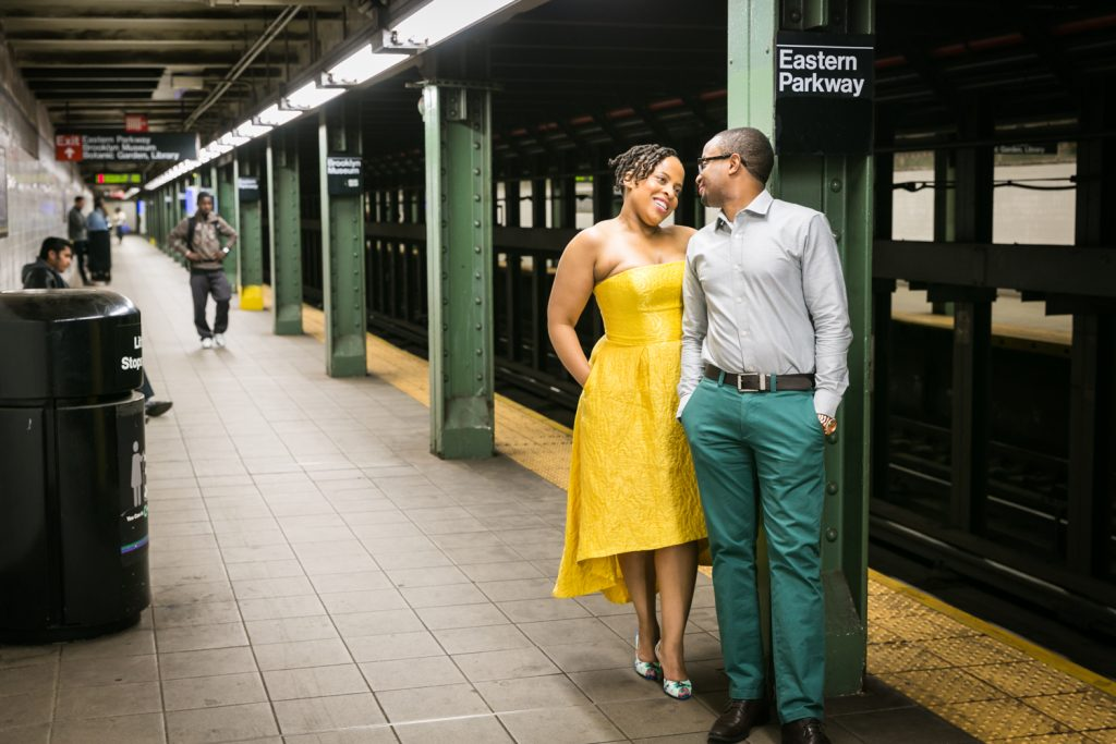 African American couple standing by column on Eastern Parkway subway platform