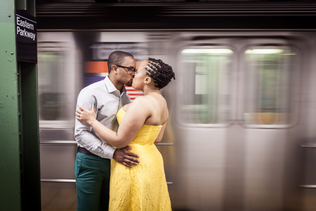 African American engaged couple kissing in front of passing subway car for an article on NYC rainy day photo tips
