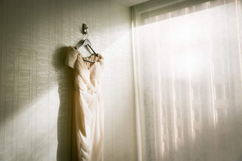 Wedding dress hanging on wall with rays of sun