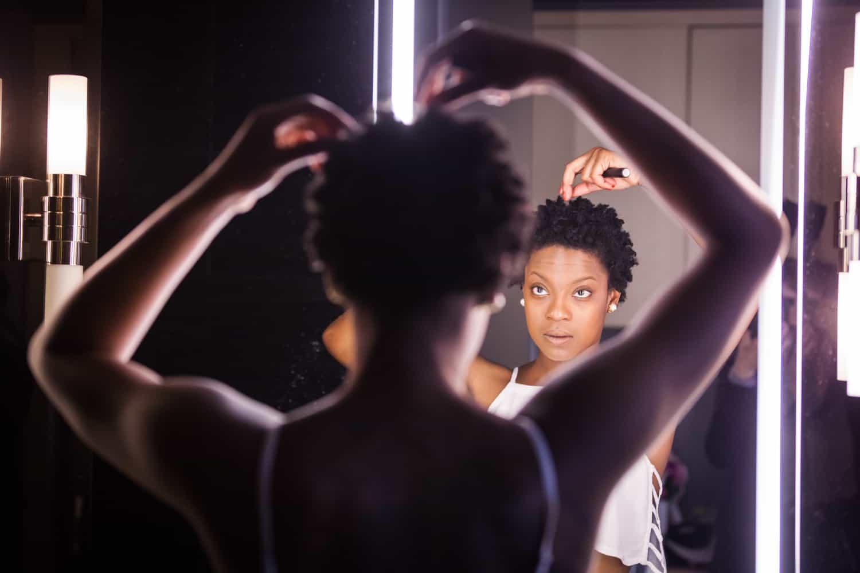 Maid of honor fixing hair in bathroom mirror