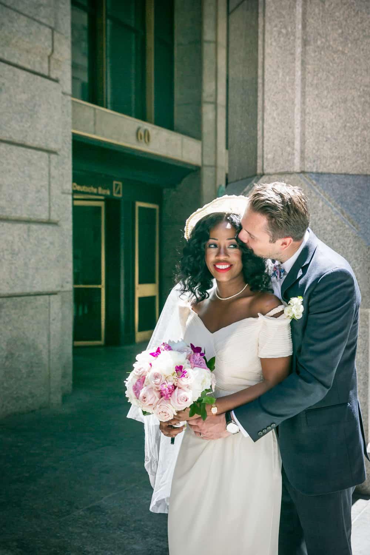 Groom kissing bride on side of head on Wall Street