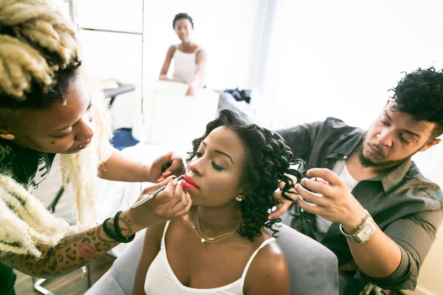 Bride getting makeup applied and hair fixed