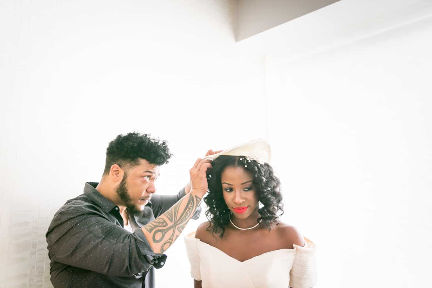 Hair stylist helping bride with hat