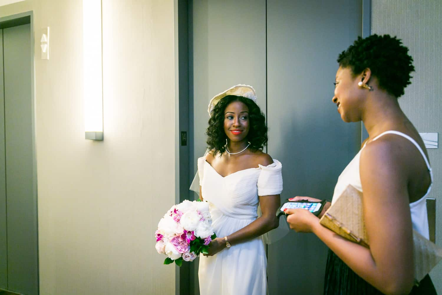 Bride looking at maid of honor in front of elevators