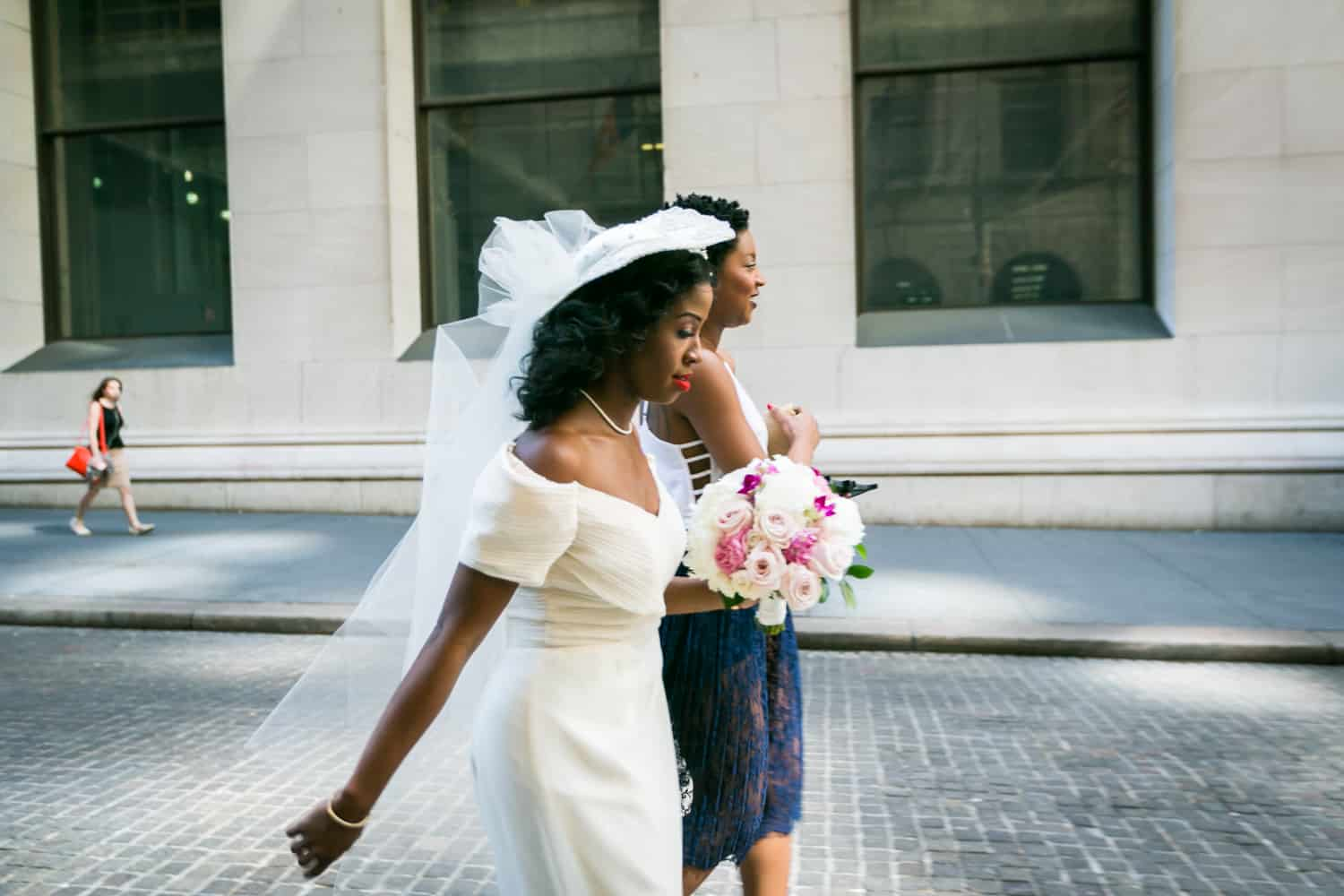 Bride and maid of honor walking to ceremony on cobblestone street