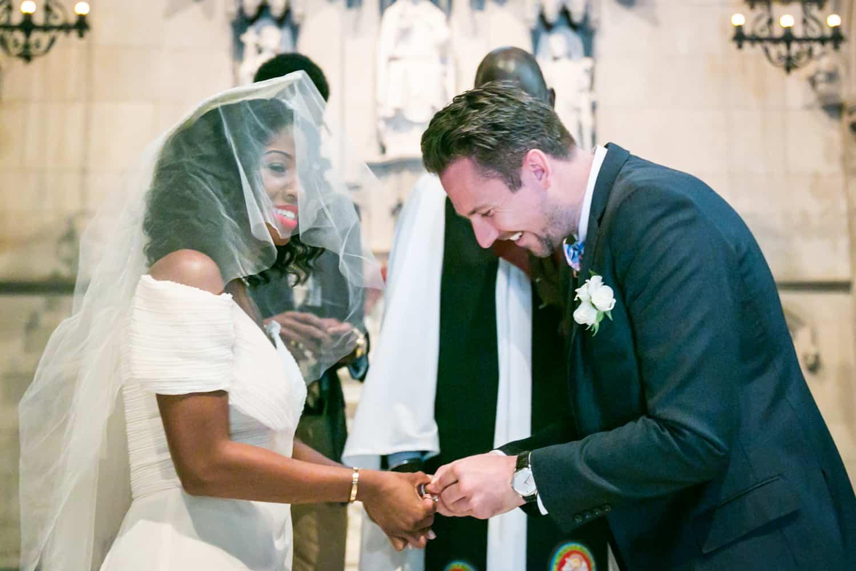 Groom putting ring on bride's finger in a Trinity Church wedding