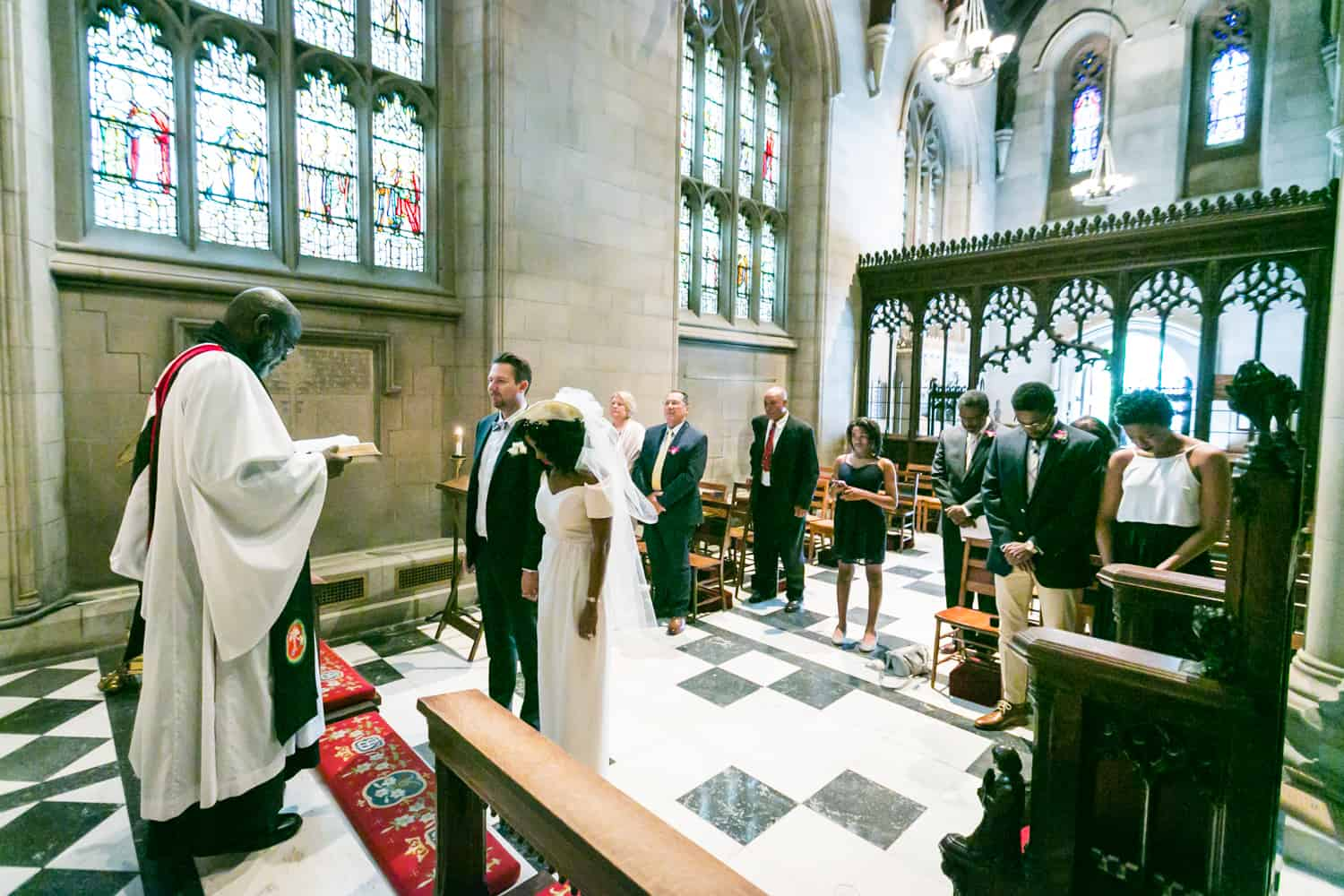 Bride and groom listening to priest during Trinity Church wedding ceremony